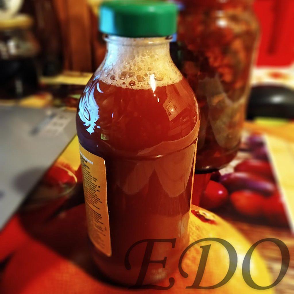 Красная жидкость в бутылке из еловых шишек